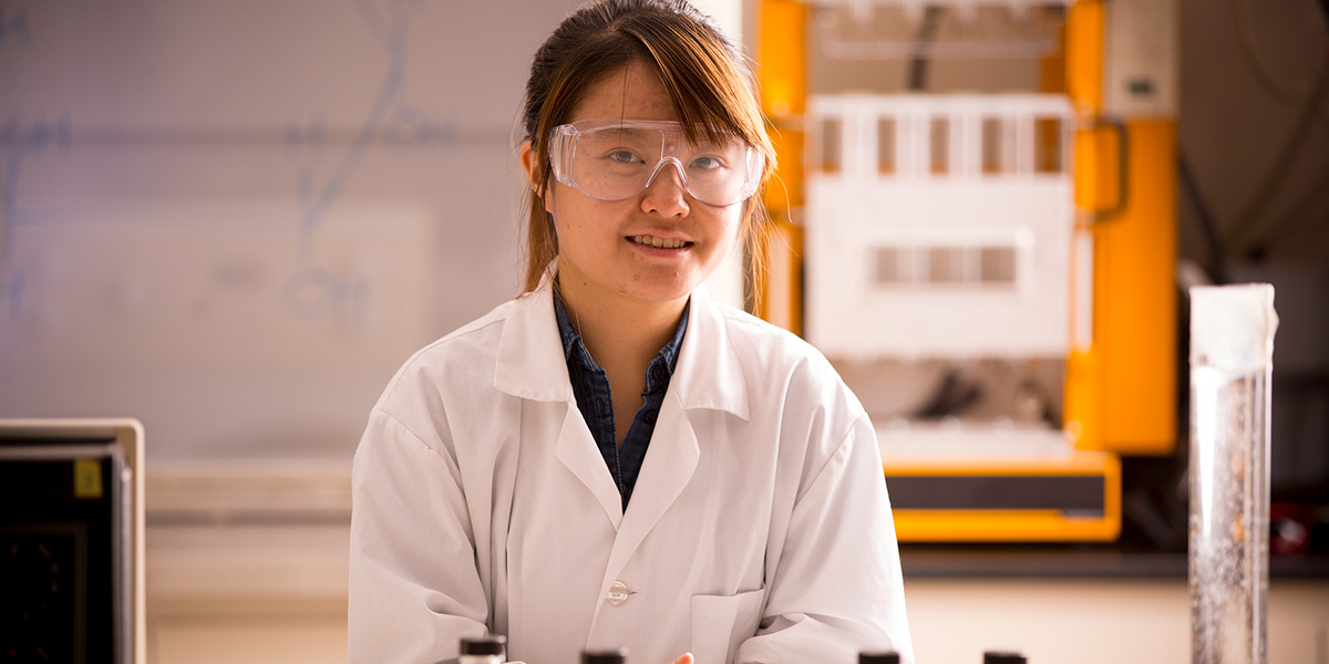 Student in the lab wearing lab coat and goggles