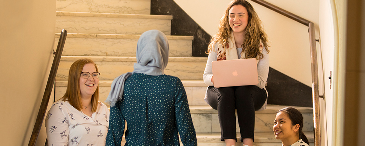 Students sitting on marble staircase using laptops